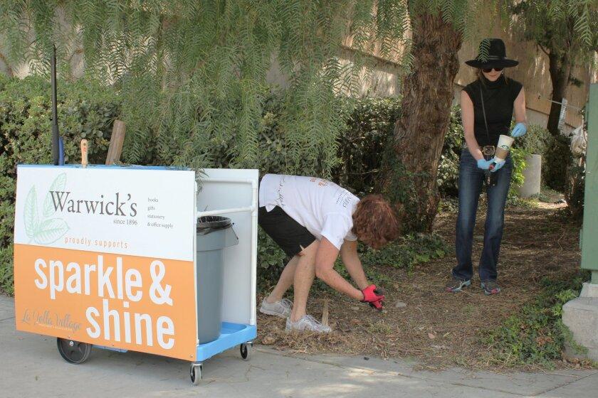 La Jolla Village Merchants Association Board member Nancy Warwick (in black) and Sparkle & Shine employee Nancy Deering pick up litter along Fay Avenue on April 1, the first day of the association's new trash collection program.