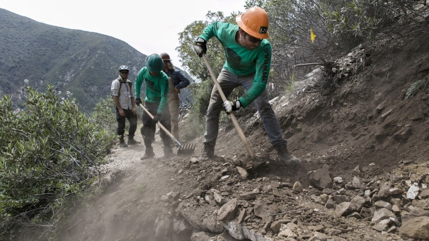 Brad Moore, 29, works on filling in the path along damaged sections of the Gabrielino Trail.