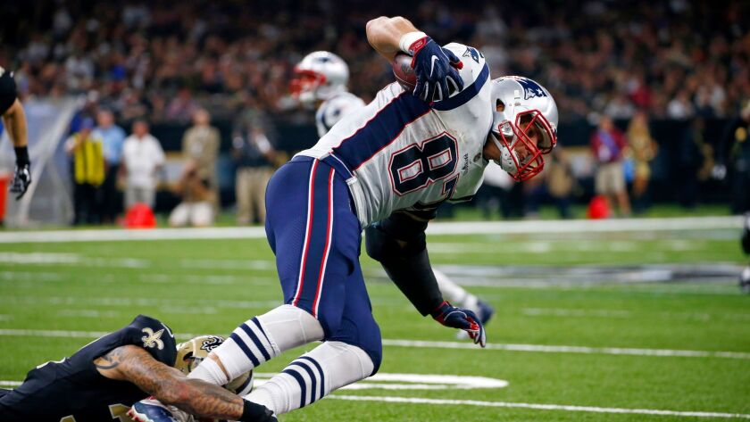 Patriots tight end Rob Gronkowski tries to break a tackle by New Orleans Saints strong safety Kenny Vaccaro in a 2017 game.
