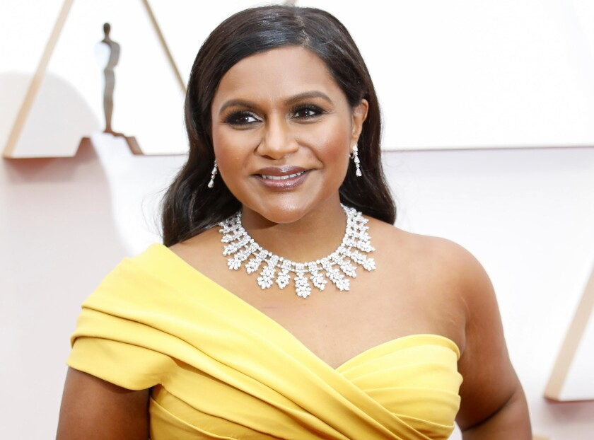 Mindy Kaling posing in a yellow dress.
