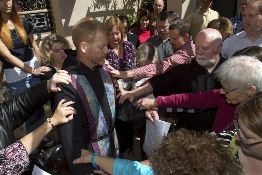 """Pastor Darryl Kistler of the Kensington Community Church is blessed by the congregation in """"the laying on of hands"""" ritual in support of his upcoming trip to Washington D.C. where he is joining in a prayer vigil Tuesday in support of gay marriage."""