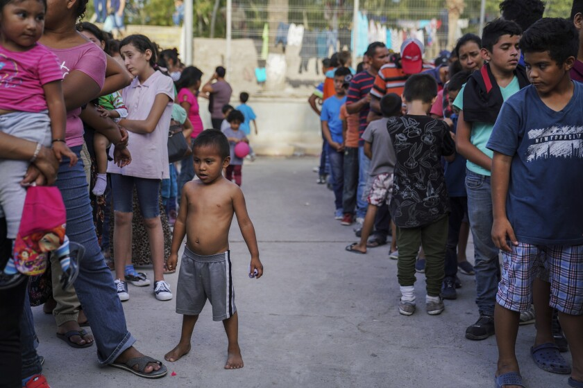 """FILE - In this Aug. 30, 2019 file photo, migrants, many who were returned to Mexico under the Trump administration's """"Remain in Mexico"""" program, wait in line to get a meal in an encampment near the Gateway International Bridge in Matamoros, Mexico. A federal appeals court has temporarily halted a major Trump administration policy to make asylum seekers wait in Mexico while their cases wind through U.S. immigration courts. A panel of the 9th U.S. Circuit Court of Appeals in San Francisco ruled Friday, Feb. 28, 2020, in a 2-1 vote to put on hold the policy that furthered President Donald Trump's asylum crackdown. (AP Photo/Veronica G. Cardenas, File)"""