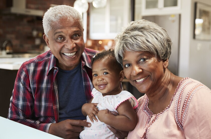 Portrait Of Grandparents Sitting With Baby Granddaughter Around Table At Home