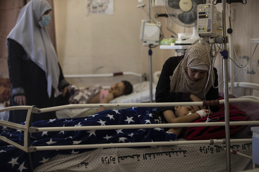 The mother of Yazan Al-zaharna, 9, comforts him as he rests at the Shifa hospital in Gaza City, Thursday, May 13, 2021, where he is receiving treatment for wounds caused by a May 10 Israeli strike that hit a nearby his family house in town of Jabaliya. Just weeks ago, the Gaza Strip's feeble health care system was struggling with a runaway surge of coronavirus cases. Now doctors across the crowded coastal enclave are trying to keep up with a very different crisis: blast and shrapnel wounds, cuts and amputations. (AP Photo/Khalil Hamra)