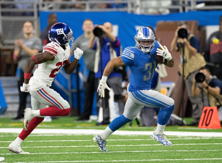Detroit Lions running back Ty Johnson, right, runs for a first down in front of New York Giants cornerback Deandre Baker during the Lions' win Sunday.