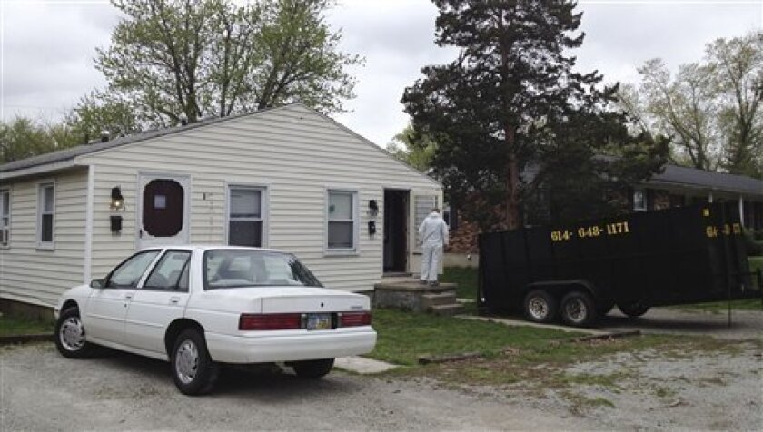 Workers clean out a home Tuesday, April 3, 2012 where 21-year-old Jessica Rae Sacco was killed Friday in Urbana, Ohio. A $100,000 bond has been set for 25-year-old Matthew Puccio, who is accused of stabbing and suffocating Sacco, then dismembering her body in their bathtub. Some of Sacco's remains were found in the apartment on Friday, March 30. Other body parts were found miles away in Kentucky. (AP Photo/Barbara Rodriguez)