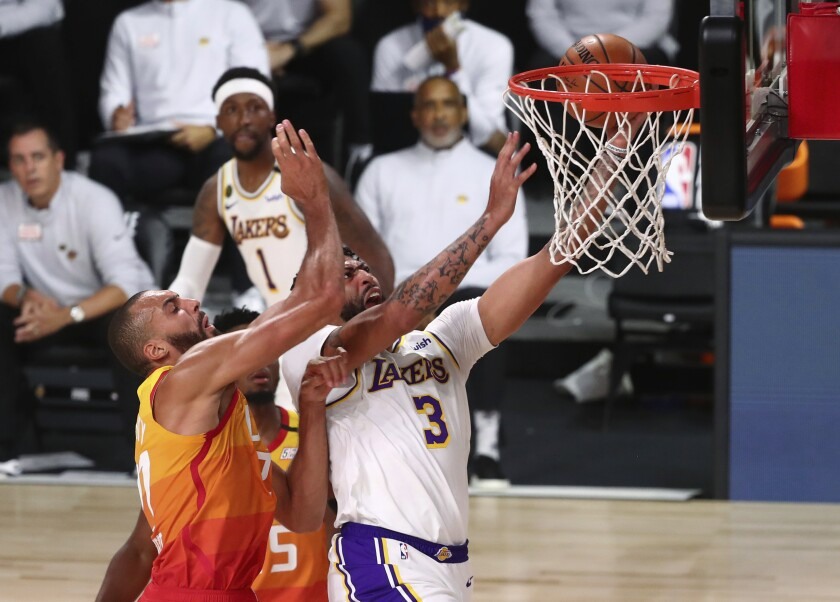 Lakers forward Anthony Davis is fouled by Utah Jazz center Rudy Gobert during the first half in Lake Buena Vista, Fla.