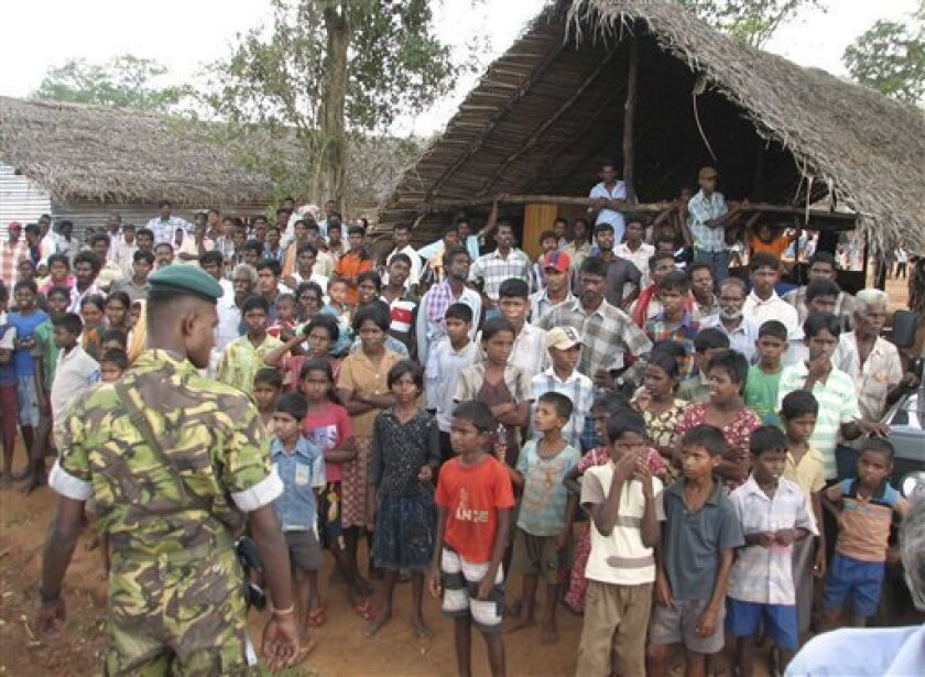 A Sri Lankan police commando stands guard as ethnic Tamils look on during the visit of French Foreign minister Bernard Kouchner, unseen, at the Manik Farm camp for internally displaced ethnic Tamils in Vavuniya, Sri Lanka, Wednesday, April 29, 2009. (AP Photo)