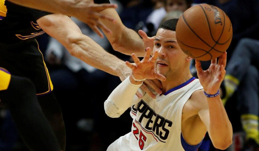 Clippers guard Austin Rivers, right, passes to a teammate after diving for a loose ball in the fourth quarter against the Lakers.