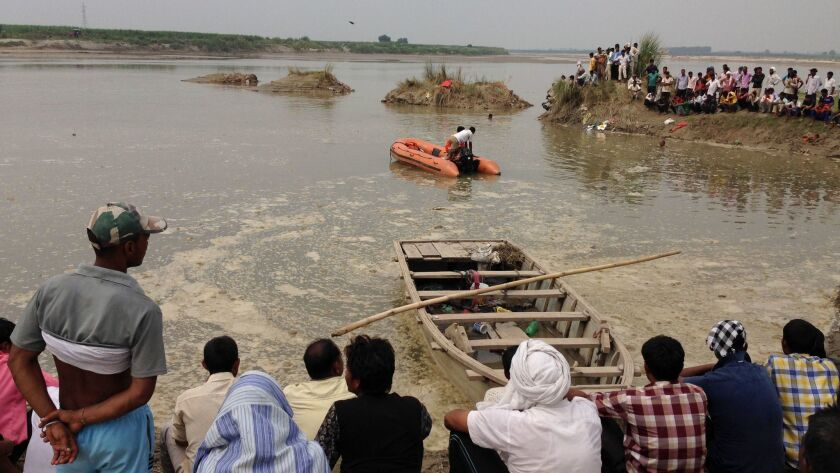 Rescuers search in the Yamuna River as villagers gather after a country boat, seen in foreground, ca