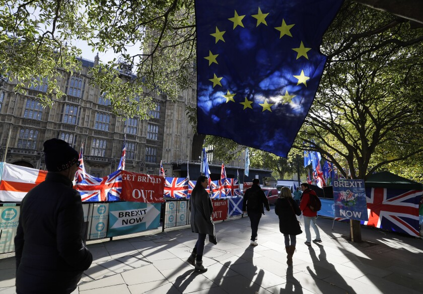 Pedestrians walk past a European Union flag outside Parliament in London.