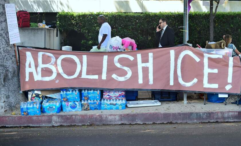 """A banner reading """"Abolish ICE"""" is displayed as immigrant rights advocates pitch their tents for an encampment outside the ICE offices in downtown Los Angeles on June 28."""