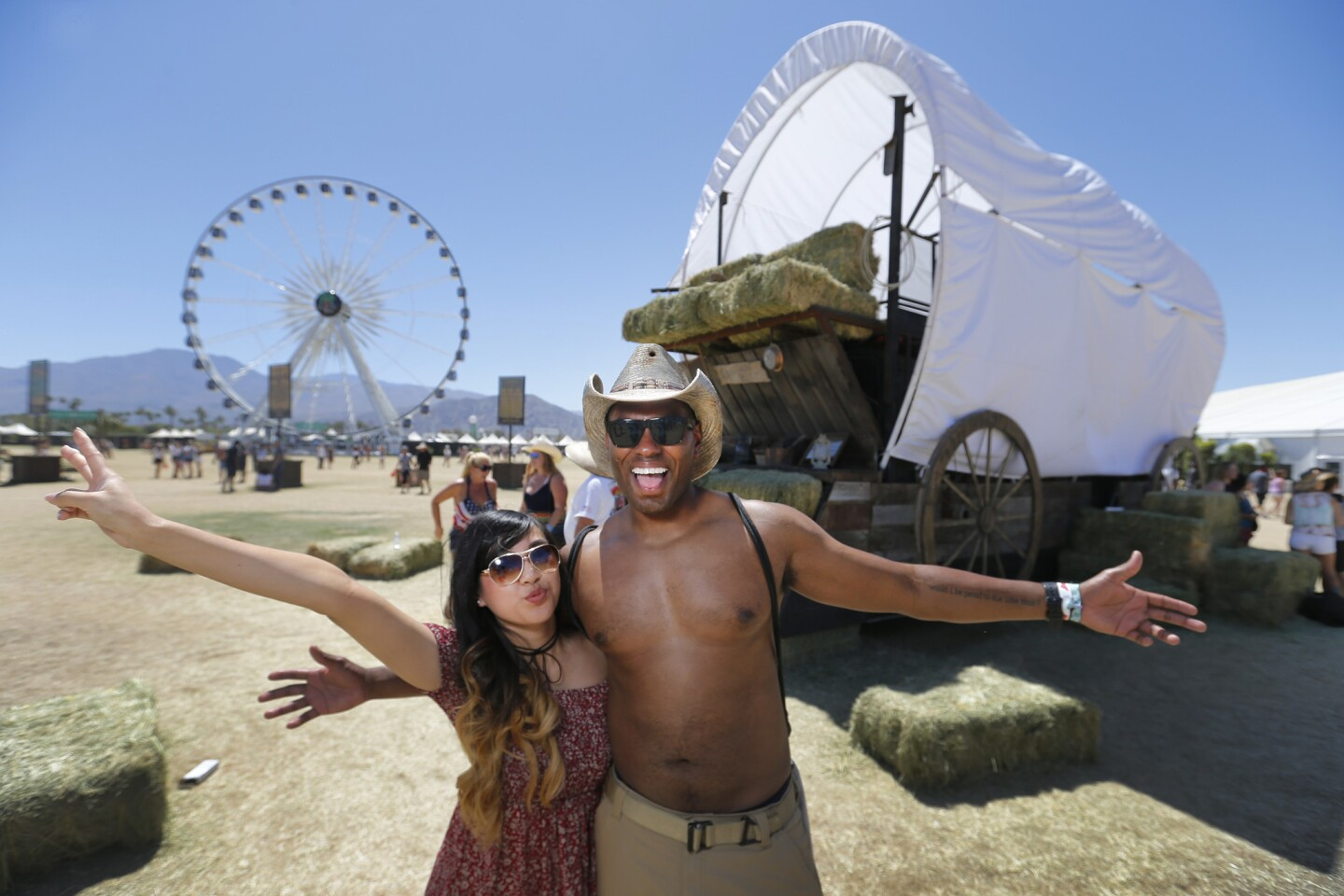 Jenn Nguyen and Amahl Harris, both of Santa Barbara, pose in front of a giant covered wagon and La Grande XL Ferris wheel on the third day of the Stagecoach country music festival at the Empire Polo Fields in Indio, Calif., on April 30, 2017.