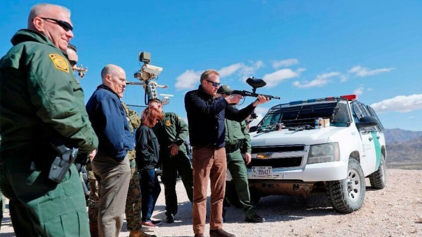 Acting Defense Secretary Patrick Shanahan fires a paintball gun modified to shoot pepper balls in Sunland Park, N.M., during a tour of the U.S.-Mexico border.