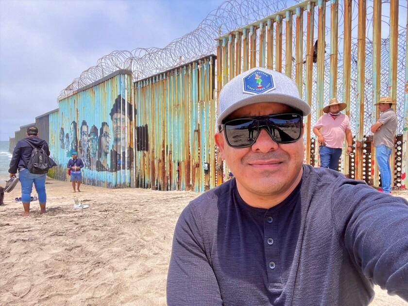 Veteran Ramon Castro by Tijuana border fence before his 1,954-mile walk June 28.