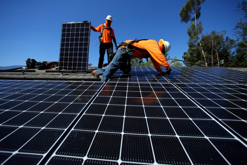 In this 2016 file photo, installers from Baker Electric place solar panels on the roof of a home in Scripps Ranch.