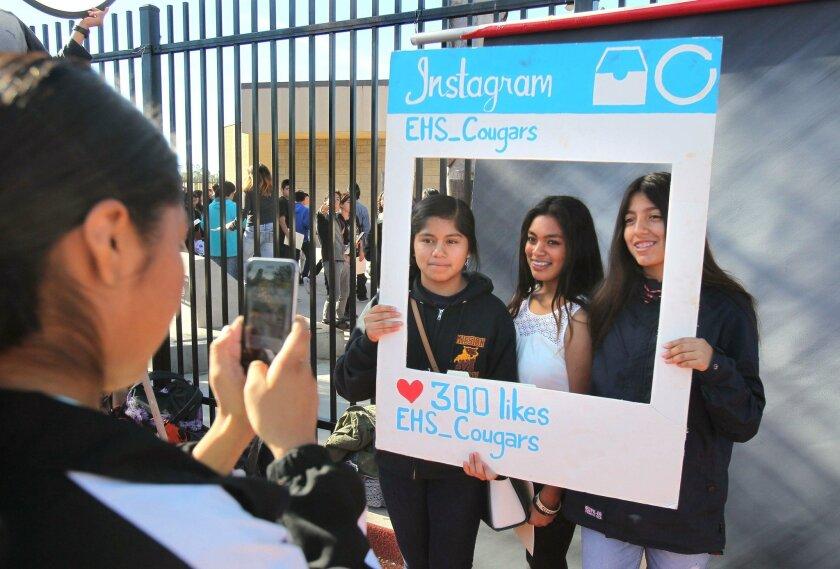 Mission Middle School students Daniella Sanchez (left), Salma Cruz, and Nancy Hernandez have their picture by Escondido High School student Albertina Estrada on Thursday.