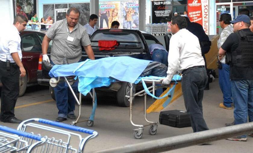 Miembros del Servicio Médico Forense realizan el levantamiento de uno de los cuerpos encontrados en Cancún. EFE/Archivo