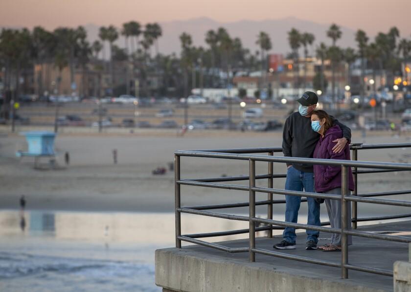 Randall and Jennifer Harris watch the sunset at the Huntington Beach Pier on Monday.