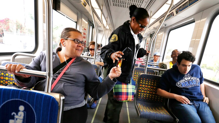 A Los Angeles County Sheriff's Department employee checks commuters' fares on an Expo Line train from Santa Monica to Los Angeles.