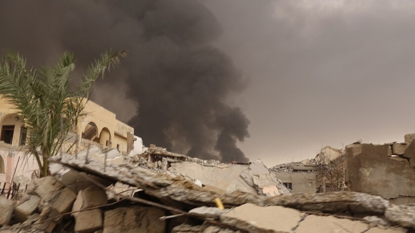 """As seen in """"Hell on Earth,"""" black smoke rises from the oil fires set by ISIS in Qayarrah village aft"""