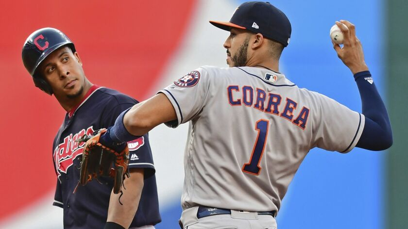 Cleveland Indians' Michael Brantley looks over at Houston Astros' Carlos Correa after Brantley hit a