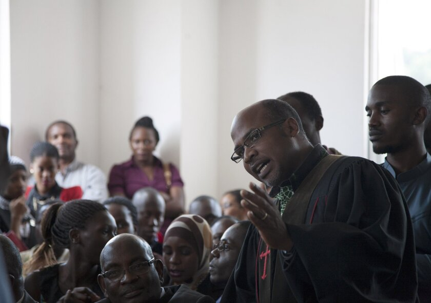Controversial Pastor and activist, Martin Ssempa right, talks to the courtroom before a judge's ruling Friday, Aug.1, 2014, at Uganda's Constitutional court . A Ugandan court on Friday invalidated an anti-gay bill signed into law earlier this year, saying the measure is illegal because it was passe