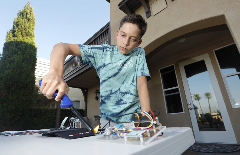 Ryan Honary, 12, prepares a demonstration of his early wildfire warning system