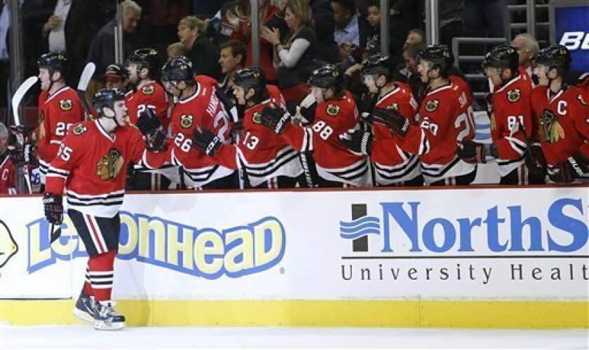 Chicago Blackhawks' Andrew Shaw gets congratulations from the bench after scoring in the first period against the Nashville Predators in an NHL hockey game in Chicago, Sunday, April 7, 2013. (AP Photo/Charles Cherney)