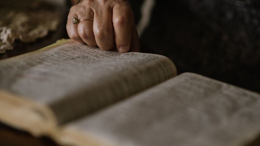 A woman reads a Bible at her home in Berryville, Va.