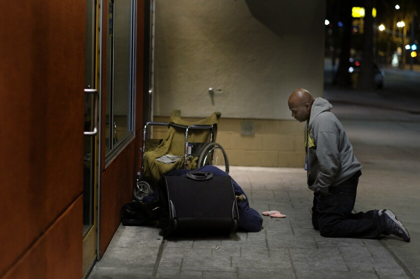 Anthony Ruffin, 48, kneels to speak with a homeless man as he is sleeping on the sidewalk in Hollywood.