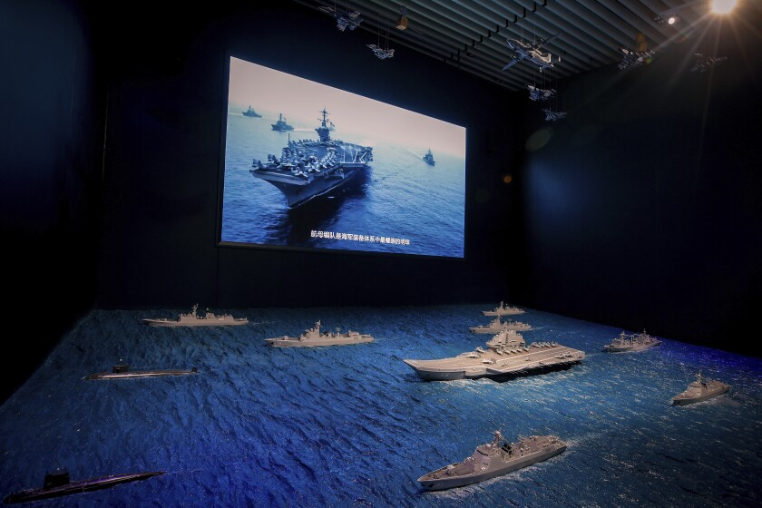 FILE - In this Aug. 1, 2019, file photo, a TV screen showing the U.S. Navy fleet sail in formation near the models of Liaoning aircraft carrier with navy frigates and submarines on display at the military museum in Beijing. China on Wednesday, May 19, 2021 protested the latest passage by a U.S. Navy ship through the Taiwan Strait, calling it a provocation that undermined peace and stability in the region. (AP Photo/Andy Wong, Fie)