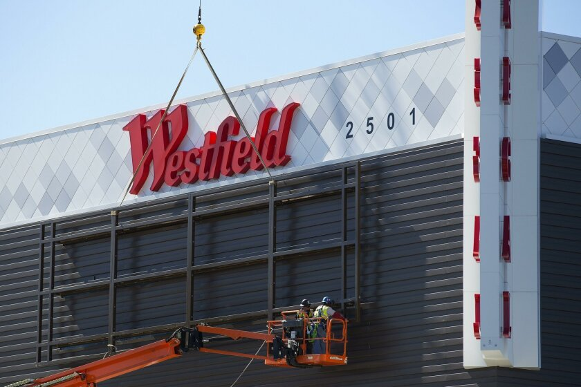 At the Westfield Carlsbad Mall in Carlsbad, workers install new signage to the exterior of the mall earlier this year where a department store had been repurposed as a multiscreen movie theater and fitness club.