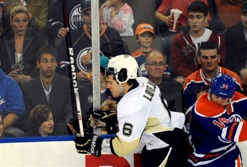 Pittsburgh Penguins' Ben Lovejoy, 6, takes a hit from Edmonton Oilers' Jordan Eberle, 14, during second period NHL hockey action in Edmonton, Alberta, on Sunday, Oct. 9, 2011. (AP Photo/The Canadian Press, Ian Jackson)