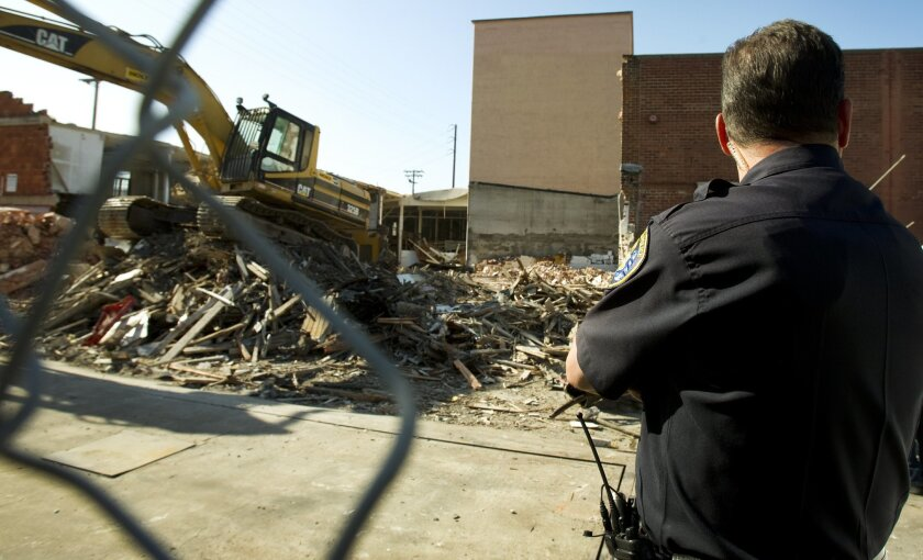 A San Diego police officer keeps an eye on a demolition site at the old San Diego Farmers Market building on Imperial Avenue in Sherman Heights. The new building will become a Walmart.
