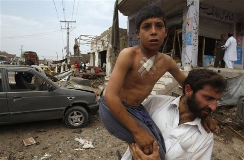 A Pakistani helps an injured boy at the site of car bombing on the outskirts of Peshawar, Pakistan, Sunday, June 2013. A car bomb exploded as a convoy of paramilitary troops passed through the outskirts of the northwest Pakistani city of Peshawar, killing more than a dozen people and wounding score