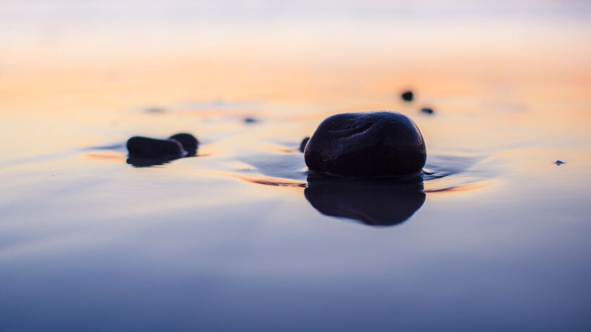 Pebbles at the beach, wet sand reflecting the evening sky after sunset. Cardiff By The Sea, Californ
