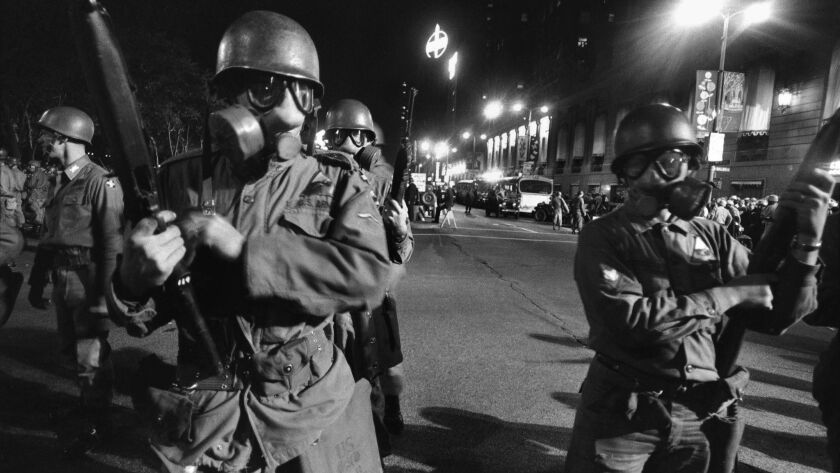 """In this file photo, National Guard troops in gas masks are posted outside the 1968 Democratic National Convention in Chicago. The riots outside the convention are one of the many devastating events featured in CNN's documentary series, """"1968: The Year That Change America."""""""