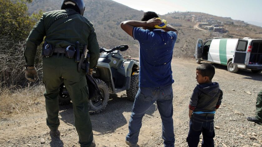 A Guatemalan father and son, who crossed the U.S.-Mexico border illegally, are apprehended by a U.S. Border Patrol agent in San Diego on June 28.