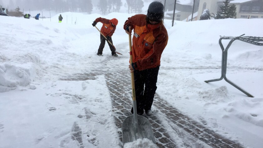 Mammoth Mountain employees clear paths as snow falls lightly Saturday morning.