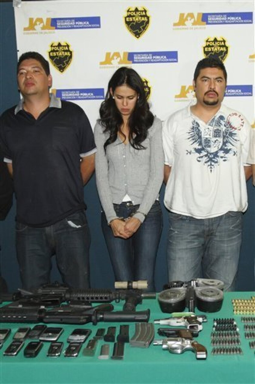 The 2008 beauty queen of the drug-plagued state of Sinaloa, Laura Zuniga, center, is shown to the press with other unidentified suspects after she was detained with guns and large amounts of cash in the city of Zapopan, Mexico, Tuesday Dec. 23, 2008. Zuniga has been arrested after she was found rid