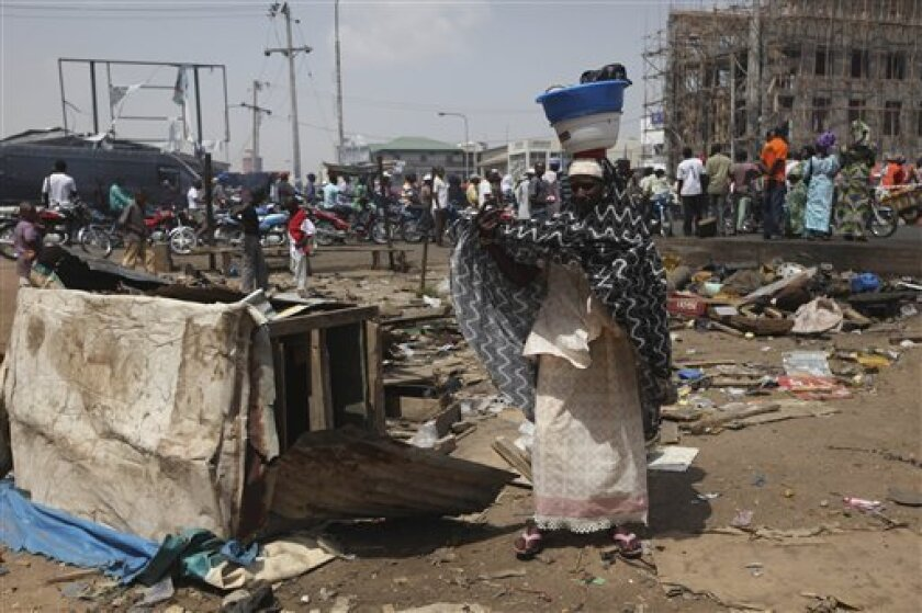 A woman stands at the scene of a bomb explosion in Kaduna, Nigeria, Monday, April 9, 2012. The weekend explosion killed at least 38 people and the target for the blast seems unclear as people from all sections of society were caught in the explosion.(AP Photos/Sunday Alamba)