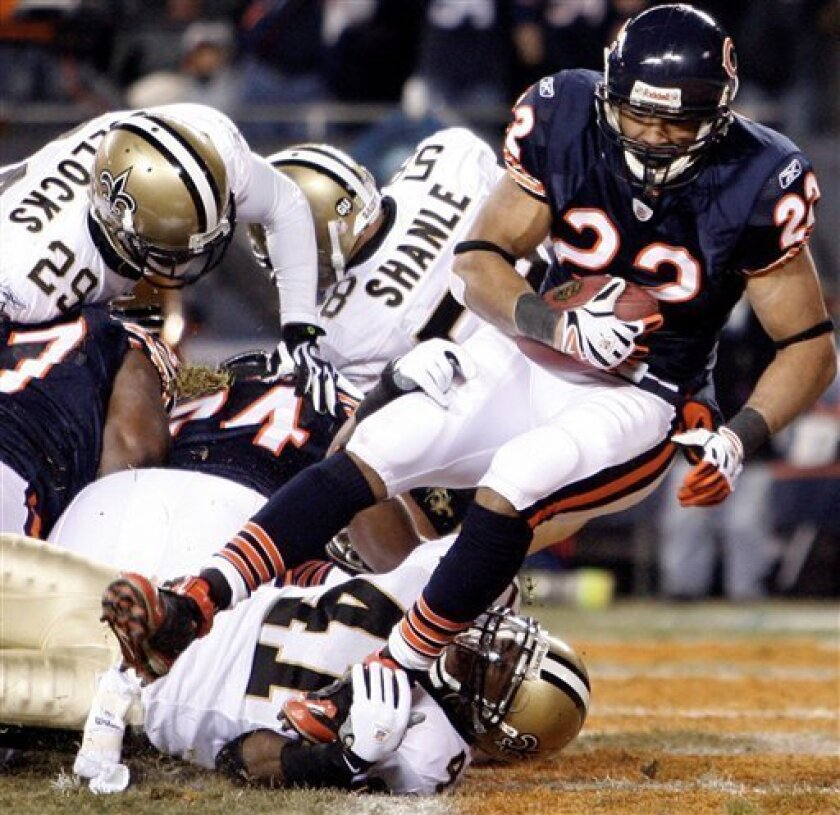 Chicago Bears running back Matt Forte (22) scores a touchdown as New Orleans Saints' Roman Harper tackles during the second quarter of an NFL football game, Thursday, Dec. 11, 2008 in Chicago.(AP Photo/Nam Y. Huh)