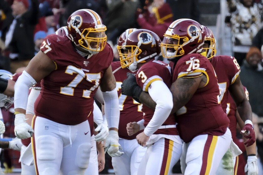 Washington Redskins kicker Dustin Hopkins, center, is congratulated by offensive guard Ereck Flowers, left, and offensive tackle Morgan Moses after kicking a field goal.