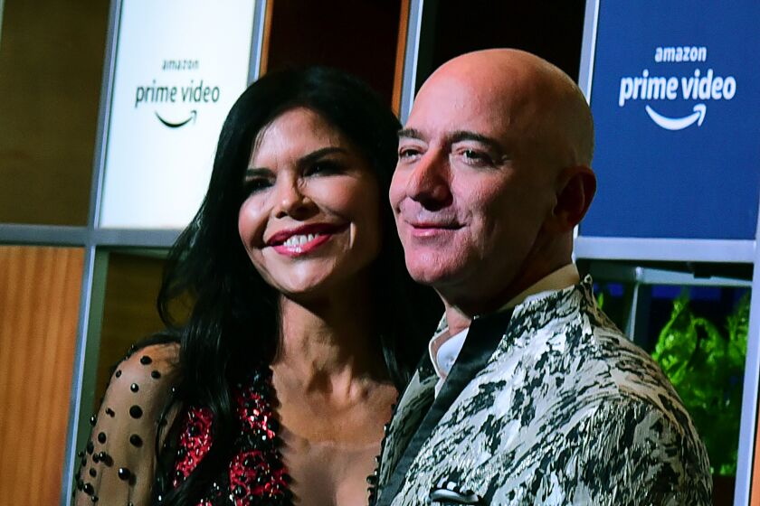 CEO of Amazon Jeff Bezos (R) and his girlfriend Lauren Sanchez (L) pose for pictures as they arrive to attend an event in Mumbai on January 16, 2020.