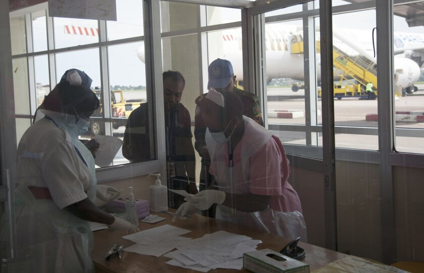 Nurses from Uganda's Ministry of Health check passengers arriving from Democratic Republic of Congo, Central Africa at Entebbe Airport Kampala Uganda, Friday, Aug. 8, 2014. A health desk has been set up at Entebbe International Airport hoping to catch those showing symptoms of the Ebola virus before entering the country. Uganda has had numerous outbreaks of the infectious and fatal disease, however has been praised for containing the virus with few casualties.(AP Photo/Rebecca Vassie)