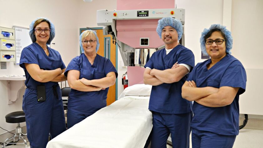 From left: Drs. Cheryl Olson, Mary K. Wilde, Ken Shimizu, and Anuradha Koka pose with a $1.5 million Mobetron machine that can speed up radiation doses for breast cancer patients.