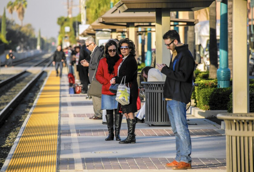Commuters wait for a train at Metrolink's Covina station last week.