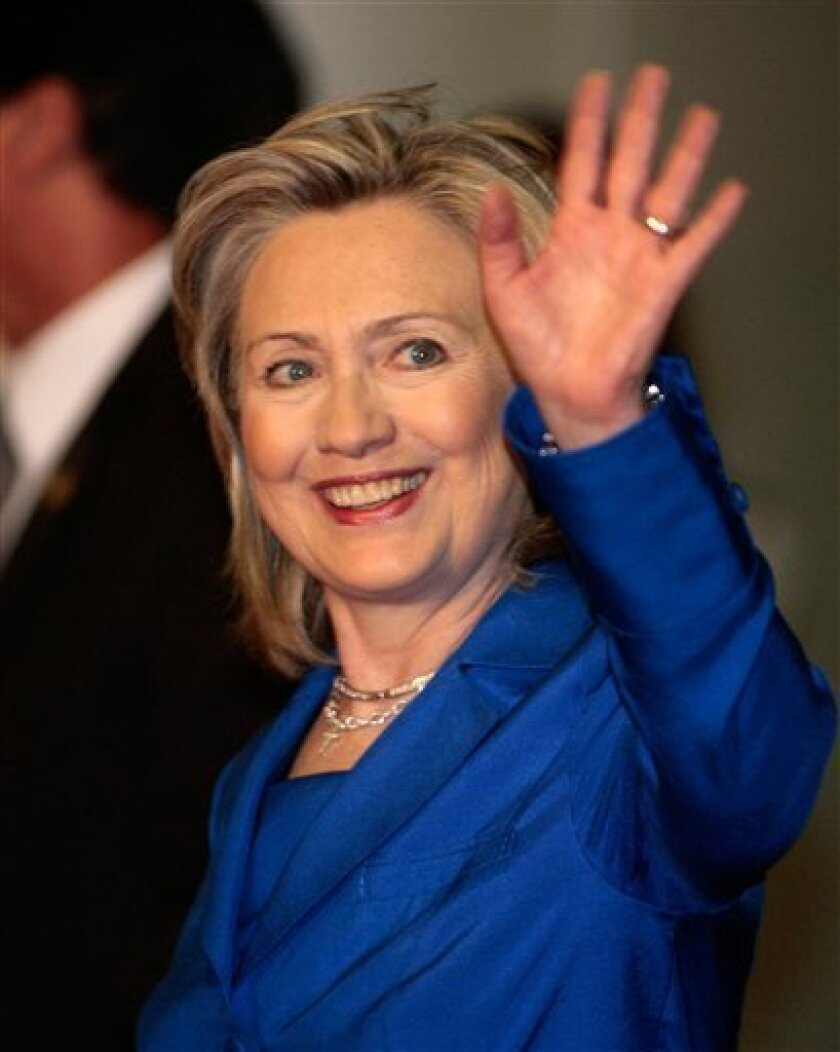 U.S. Secretary of State Hillary Rodham Clinton waves to journalists at the Brazil's National Congress in Brasilia, Wednesday, March 3, 2010. Clinton is on a two-day official visit to Brazil. (AP Photo/Eraldo Peres)