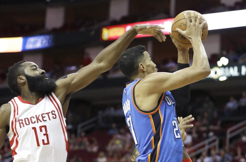 Oklahoma City Thunder's Andre Roberson, right, shoots as Houston Rockets' James Harden (13) defends in the first half of an NBA basketball game Monday, Nov. 2, 2015, in Houston. (AP Photo/Pat Sullivan)